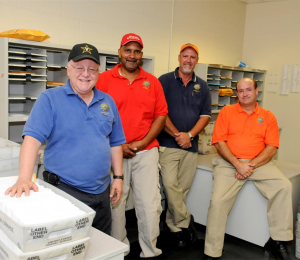 four men in Postal Services work area